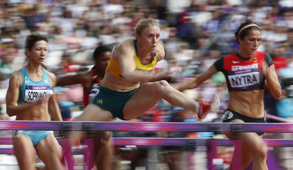 Australia's Sally Pearson of clears a hurdle with Kazakhstan's Anastasiya Soprunova and Germany's Carolin Nytra in their round 1 women's 100m hurdles heat during the London 2012 Olympic Games at the Olympic Stadium