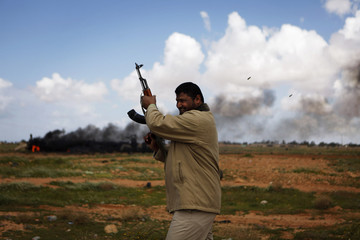 A rebel fighter fires his weapon into the air near Benghazi