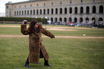 Fan wearing an animal print coat throws a football outside the stadium before the football game between Harvard and Yale Universities at Harvard in Cambridge