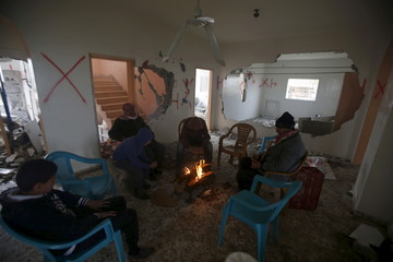 Palestinians warm themselves by a fire inside the home of Palestinian Mohammed al-Haroub after it was partially demolished by Israeli army in the West Bank village of Dir Samt, south of Hebron
