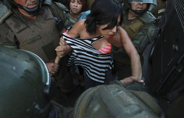 A protester is detained by riot police while demostrating in Santiago