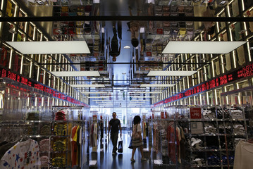 Shoppers walk in Fast Retailing's Uniqlo casual clothing store in Tokyo