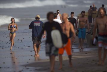 A woman jogs around a crowd of beachgoers as she runs along the beach in Encinitas, California