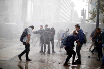 "Demonstrators are sprayed by a riot police water cannon during a ""Reflexive strike of students"" called by the Chilean student federations to request better and more changes in the education system in Santiago"