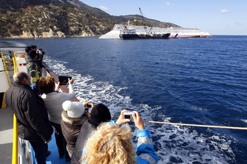 People take pictures from a ferry of capsized cruise liner Costa Concordia at Giglio island