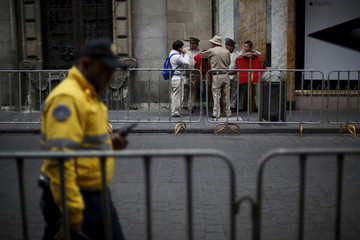 Musicians speak to each other behind fences placed along a street in preparation for the upcoming visit of Pope Francis at the perimeter of Zocalo Square in Mexico City