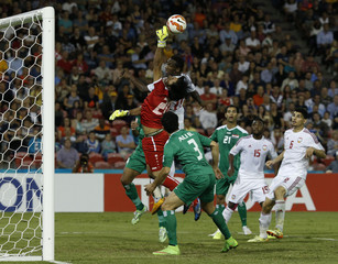 Iraq's goalkeeper Mohammed Hameed Farhan jumps for the high ball with UAE's Ahmed Khalil during their Asian Cup third-place playoff soccer match at the Newcastle Stadium in Newcastle