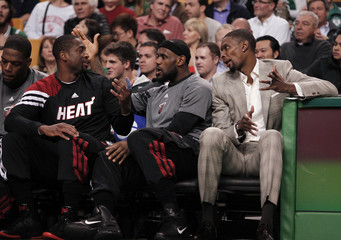 Miami Heat players Dwyane Wade, LeBron James, and Chris Bosh talk on the bench as they sit out their NBA basketball game against the Boston Celtics in Boston