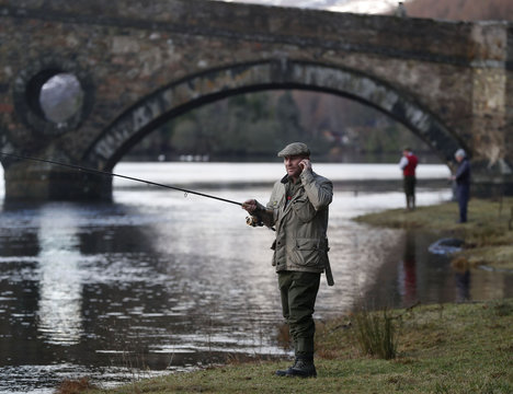 An angler speaks on his mobile phone as he fishes on the opening day of the salmon fishing season on the River Tay at Kenmore in Scotland
