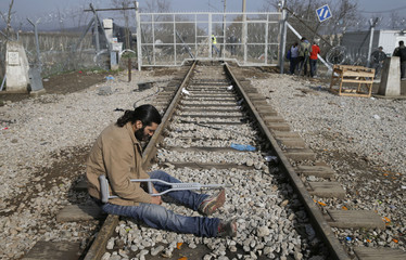 Young migrant sits on a disused railway track next to the Greek-Macedonian border fence at a camp near the Greek village of Idomenii
