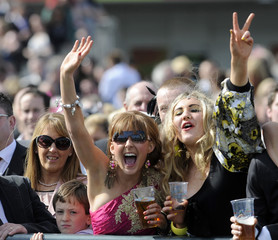 Race-goers cheer on the horses during the first day of The Grand National Meeting at Aintree Racecourse, Liverpool, northern England