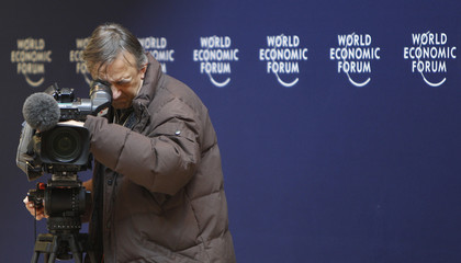 A cameraman films inside the congress centre of Davos