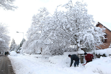Margaret and George Finlay clear away snow from their home, in Dunblane, Scotland