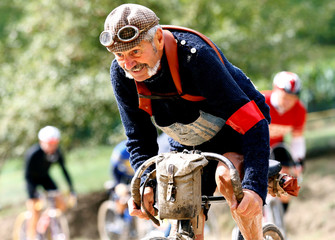 """Luciano Berruti rides a vintage bicycle on gravel roads during the Strade Bianche section of the """"Eroica"""" cycling race for old bikes in Gaiole in Chianti"""