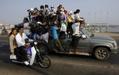 Cambodians sit on taxi as they leave Phnom Penh to return to their hometowns to celebrate Khmer New Year