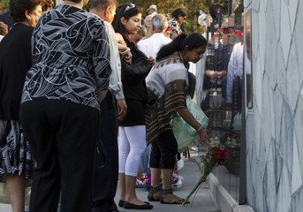 People lay flowers at the Air India monument after the 25th anniversary memorial gathering in Toronto