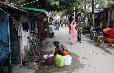 A woman washes clothes outside her house at a slum in New Delhi