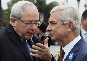 French National Assembly President Claude Bartolone listens to the President of the Ile de France Regional Council Jean-Paul Huchon as they arrive to attend a ceremony to mark 70 years since the victory over Nazi Germany during World War Two