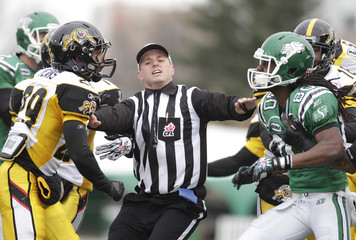 A referee tries to stop a fight between Tiger Cats Means and Roughriders wide receiver Hill during second half CFL football game in Regina