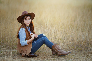 Beautiful womam sensuality elegance woman cowgirl on during sunset, Clothed blue jeans, brown leather jacket and hat. Has slim sport body. Portrait nature.  vintage style