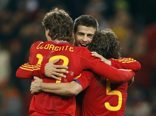 Spain's Llorente, Pique and Puyol hug after the 2010 World Cup second round soccer match between Spain and Portugal at Green Point stadium in Cape Town