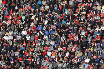 Spectators shield their eyes from the glare of the Sun during the first round Copa America 2015 soccer match between Uruguay and Paraguay at Estadio La Portada in La Serena