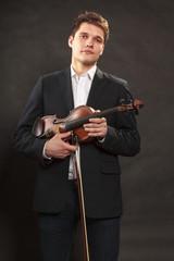 Man man dressed elegantly holding violin