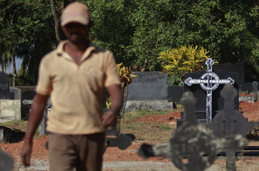 A worker walks past graves at a cemetery where the last rites for nurse Jacintha Saldanha would be performed, in Shirva