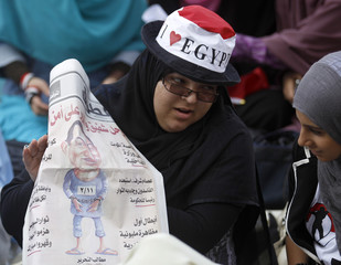 A woman shows her friend a newspaper with a cartoon of former president Hosni Mubarak in handcuffs during a pro-democracy rally at Tahrir Square