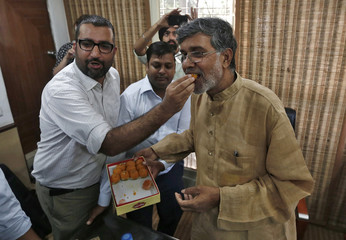 Indian children's right activist Satyarthi is offered sweets by a well-wisher at his office in New Delhi