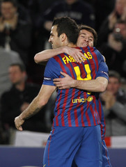 Barcelona's Messi is congratulated by team mate Fabregas after scoring a goal against Bayer Leverkusen during their Champions League last 16 second leg soccer match in Barcelona