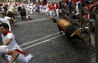 Fuente Ymbro fighting bull slides against the protective barrier at the Estafeta curve during the third running of the bulls at the San Fermin festival in Pamplona