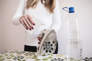 Young woman putting distilled water into iron.