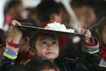 An ethnic Miao minority child wearing traditional costume carries a plate of rice during lunchtime at the village of Basha in Congjiang county