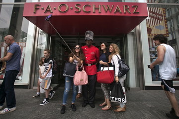 A toy soldier poses for photos outside the flagship FAO Schwarz, the oldest toy store in the United States, is pictured in the Manhattan borough New York