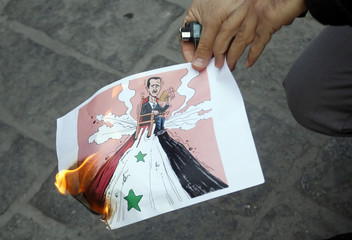 A Syrian living in Turkey burns a cartoon of Syria's President Bashar al-Assad during a protest in Istanbul