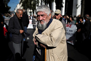 A Greek pensioner leans on a shepherd's crook during a demonstration against planned pension cuts in Athens