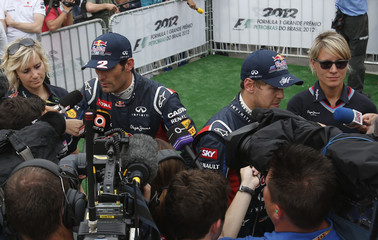 Red Bull Formula One drivers Mark Webber of Australia and Sebastian Vettel of Germany are interviewed after the qualifying session of the Brazilian F1 Grand Prix