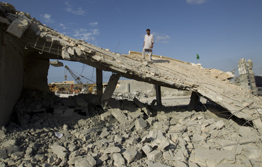 A man stands on the remnants of a school and mosque bombed by NATO forces according to Libyan officials in a village on the outskirts of Zlitan