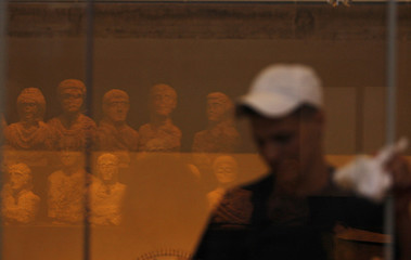 A museum worker cleans a glass display case at the Israel Museum in Jerusalem