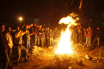 Relatives of Palestinian prisoners stand around a bonfire as they wait for their release in Ramallah