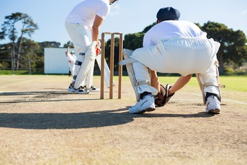 Rear view of wicket keeper crouching by stumps during match