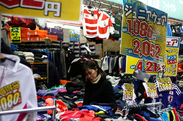 A woman chooses clothes at a shop in Tokyo
