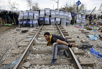 Iranian migrant reacts in front of Macedonian police at the Greek-Macedonian border
