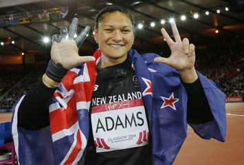 Adams of New Zealand celerbates her gold medal finish with the flag after the Women's Shot Put final at the 2014 Commonwealth Games in Glasgow