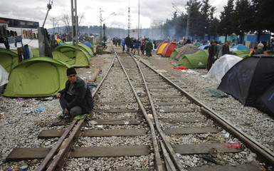 A migrant sits on railway tracks at a makeshift camp on the Greek-Macedonian border near the village of Idomeni
