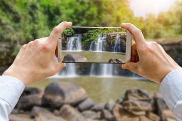 Cropped shot view of man's hands making photo on mobile phone camera of Small waterfall on the rock