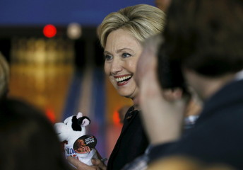 Clinton holds a stuffed cow toy given to her by a supporter in the crowd during a campaign stop at a bowling alley in Adel, Iowa