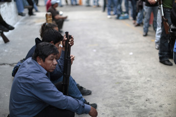 People sit and wait to register their weapons outside DIGECAM office in Guatemala City
