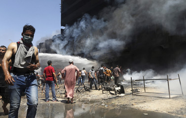 Firefighters and vendors work to extinguish a blaze at a carpet market in Benghazi